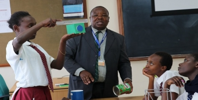 Mr. Simon Mugoh National Trainer CEMASTEA explaining cross sectional area in solids during a school visit at CEMASTEA