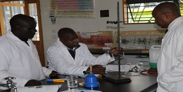 Mr. Samuel Gachuhi, Dean Chemistry Department (right) guides participants through the improvised Liebig condenser using locally available materials