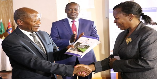 Hon. Dr. J.C Muyingo State Minister for Higher Education, Uganda handing over the Strategic Plan to Director CEMASTEA Mrs. Jacinta L. Akatsa. Looking over is Director for Secondary Education Paul Kibet, OGW