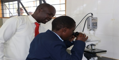 Mr. Paul Akoko (left) instructing a learner on how to use the light microscope