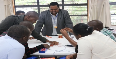 Mr. Ernest Ng'eny (middle) dean Physics Department at CEMASTEA guiding the participants on the clip motor during the training on Quality Gender- Responsive STEM Education at CEMASTEA