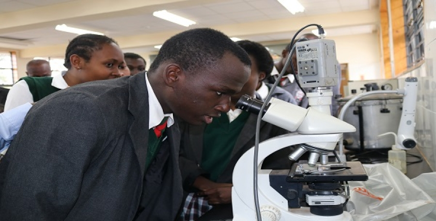 Thika High school Students performing an experiment using Triocular Light Microscope at CEMASTEA'S biology laboratory during a School visit